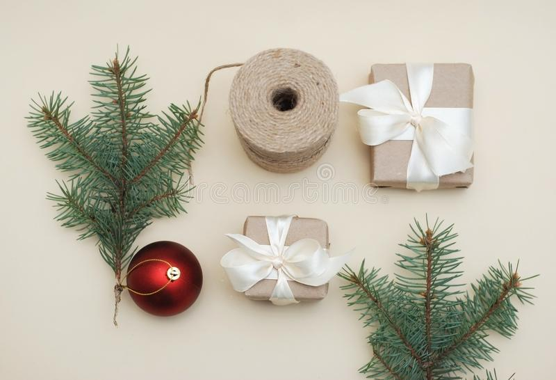 Conceito do Natal Presente envolvido no papel e amarrado com mentiras brancas da fita perto do ramo de ChristmasFir e do globo ve imagem de stock