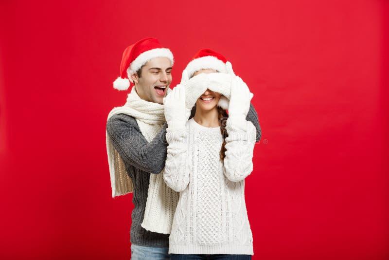 Conceito do Natal - retrato de uma amiga surpreendente do noivo novo romântico sobre o fundo vermelho do estúdio imagem de stock