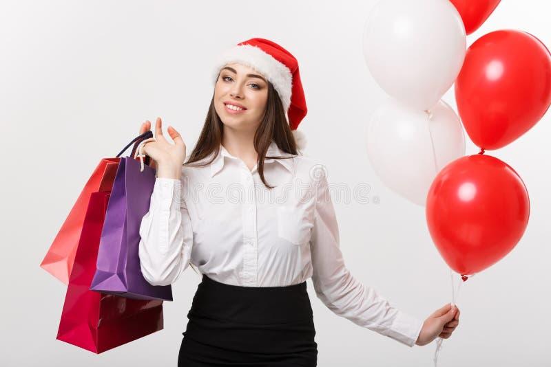 Conceito do Natal - sacos de compras guardando felizes caucasianos bonitos e ballons da mulher de negócio foto de stock royalty free