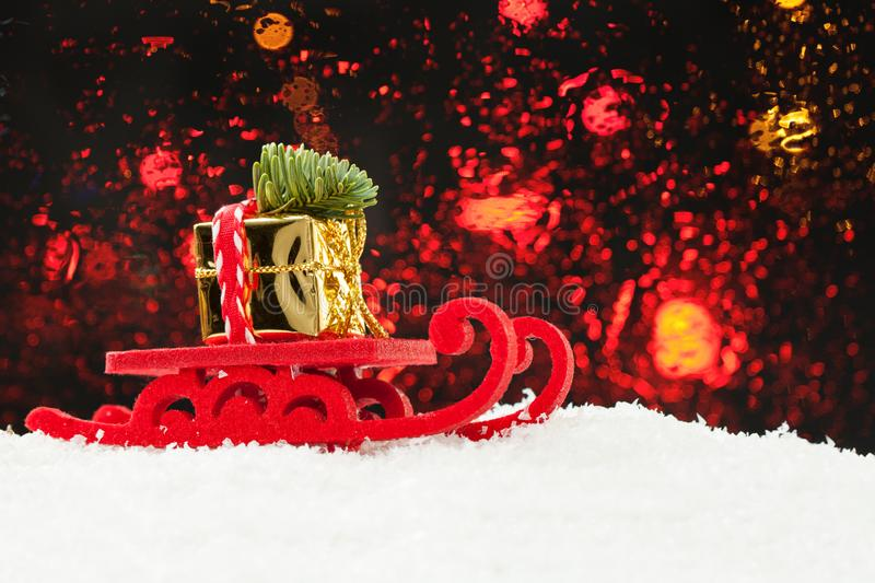 Conceito do Natal Trenó de Santa que conduz o presente do ouro e a árvore do Xmas contra o fundo abstrato da luz do bokeh imagens de stock royalty free