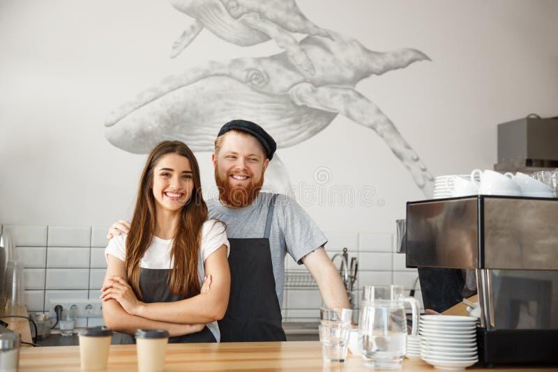 Conceito do negócio do café - o homem farpado novo positivo e os pares atrativos bonitos do barista da senhora apreciam trabalhar imagem de stock