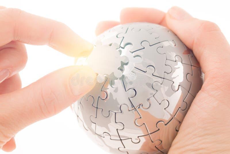 Conceito do negócio com um globo do enigma do edifício da mão fotografia de stock royalty free