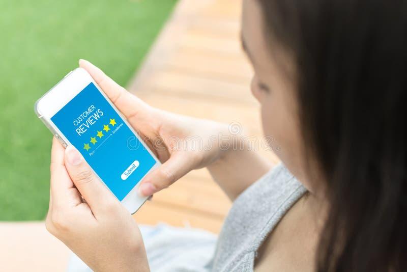 Conceito do negócio da avaliação da revisão do cliente, mão da mulher usando o móbil imagem de stock