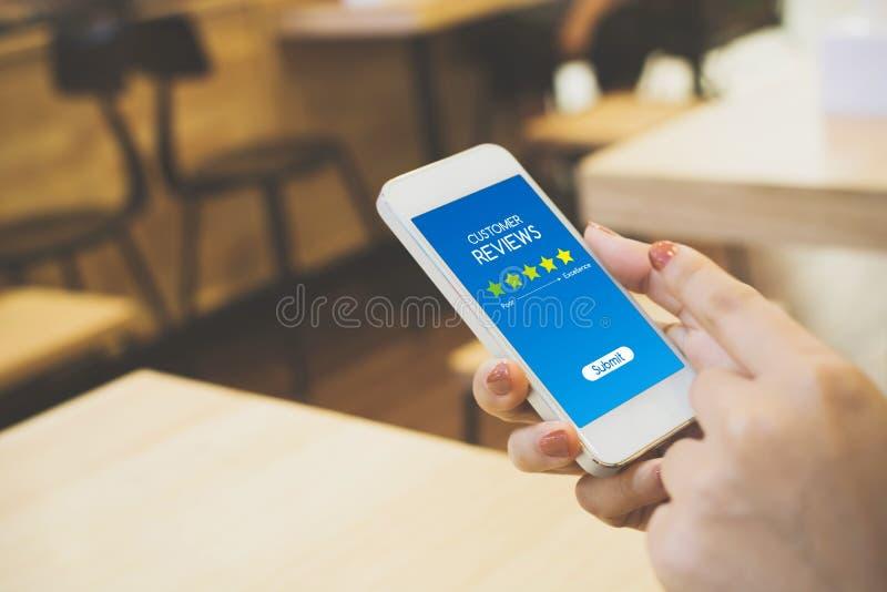 Conceito do negócio da avaliação da revisão do cliente, mão da mulher usando o móbil fotos de stock royalty free