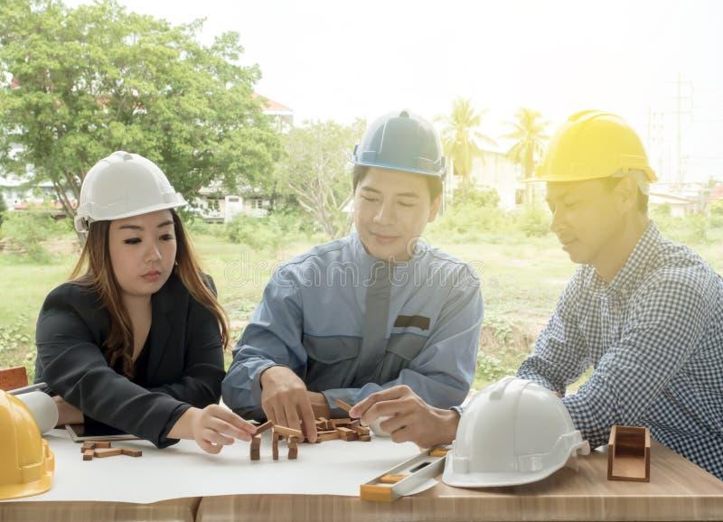 Conceito do negócio, da construção, dos trabalhos de equipe e dos povos - o grupo está discutindo o plano da construção do projet fotos de stock