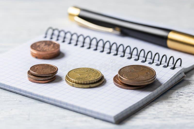 Conceito do negócio, da finança ou do investimento Moedas, livro de cheques ou caderno e pena de fonte Fundo de madeira branco fotos de stock
