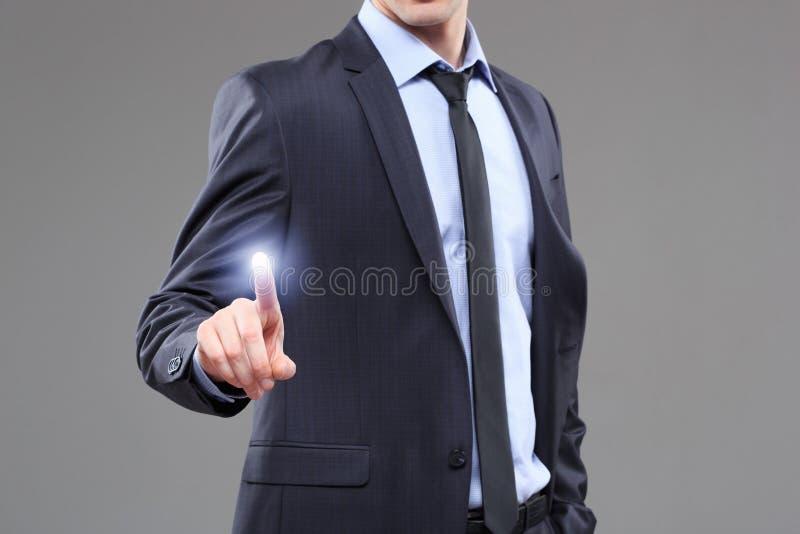 Conceito do negócio, da tecnologia, do Internet e dos trabalhos em rede - homem de negócios que pressiona o botão com contato em  imagem de stock
