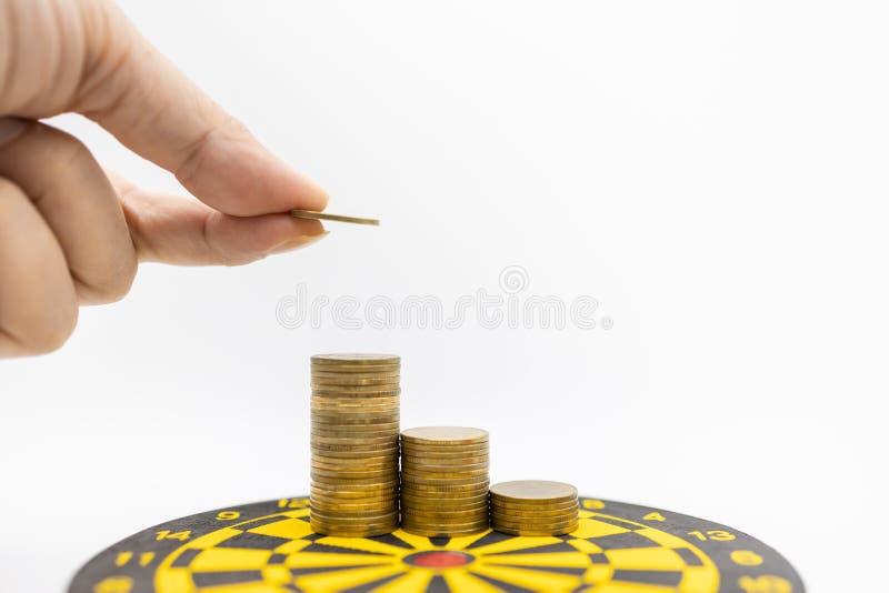 Conceito do negócio, do dinheiro, do planeamento e do salvamento Feche acima da mão do homem que guarda uma moeda de ouro e põe-n fotografia de stock