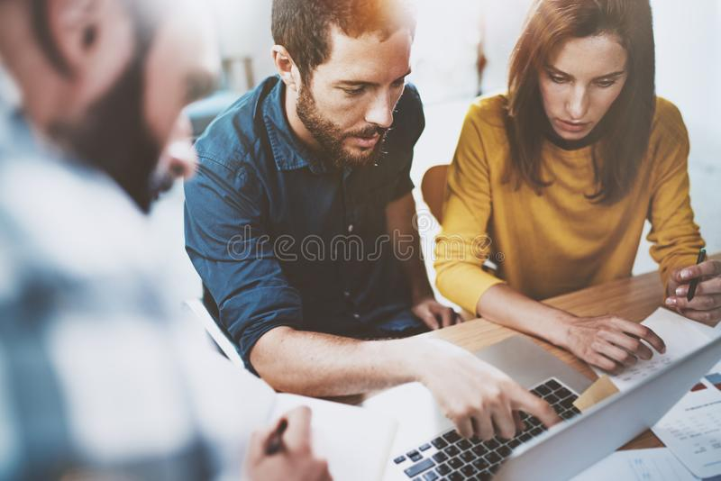 Conceito do negócio dos trabalhos de equipa Colegas de trabalho novos que sentam-se no escritório da reunião e que usam o portáti foto de stock