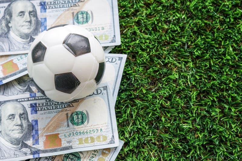 Conceito do negócio do futebol: Um fooball em notas de dólar e em verde foto de stock royalty free