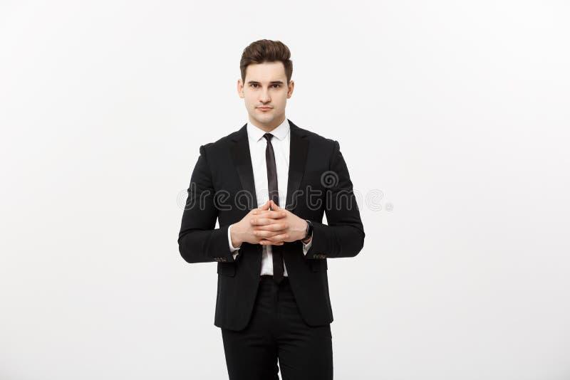 Conceito do negócio - homem de negócio considerável do retrato no terno que guarda as mãos com cara segura Fundo branco imagem de stock