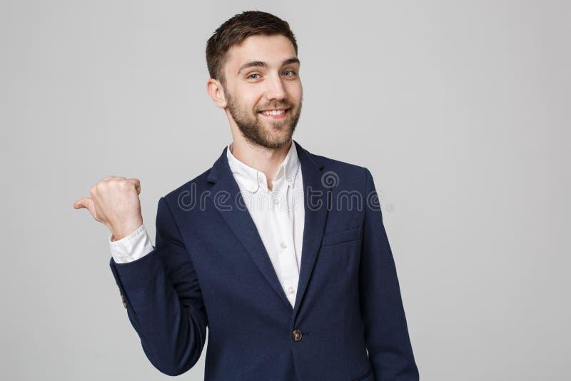 Conceito do negócio - homem de negócios bem sucedido novo do retrato que aponta o dedo sobre o fundo escuro Copie o espaço imagens de stock