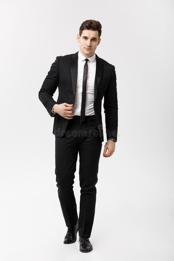 Conceito do negócio: Imagem completa do retrato do comprimento de um homem de negócio elegante no terno esperto que anda no fundo fotos de stock