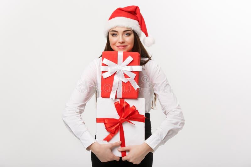Conceito do negócio - mulher de negócio caucasiano nova bonita com o chapéu de Santa que guarda muitas caixas de presente com esp fotografia de stock royalty free