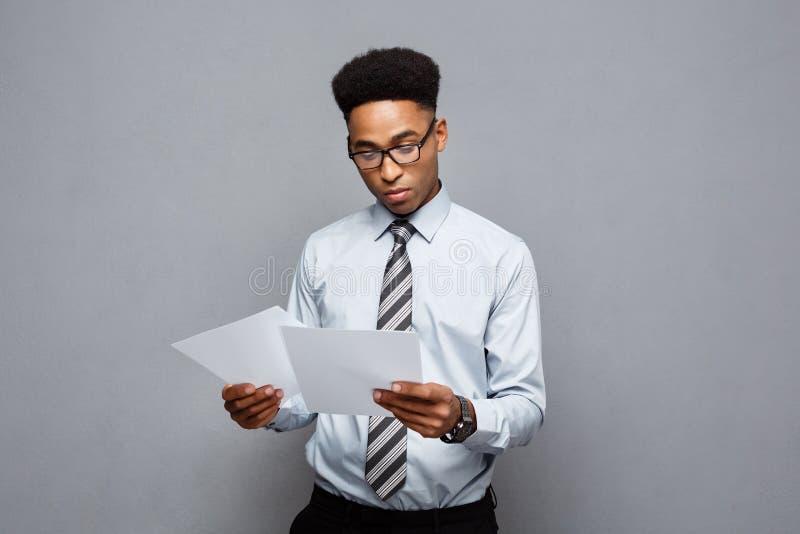 Conceito do negócio - o homem de negócios afro-americano profissional novo considerável concentrou a leitura no papel do original fotos de stock