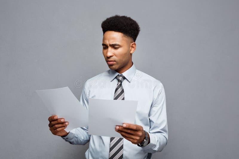 Conceito do negócio - o homem de negócios afro-americano profissional novo considerável concentrou a leitura no papel do original fotografia de stock royalty free