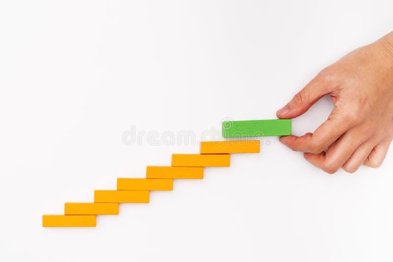 Conceito do negócio para o processo do sucesso do crescimento, mão que empilha o bloco de madeira como a escada da etapa imagens de stock