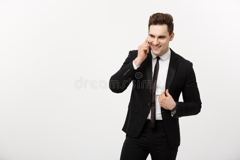 Conceito do negócio: Retrato de um homem de negócios alegre no terno esperto que fala no telefone esperto isolado em um branco fotos de stock royalty free
