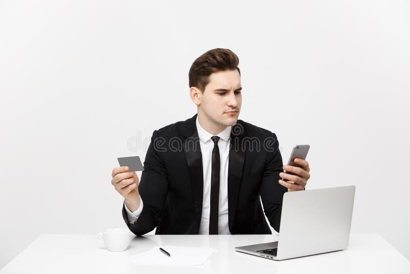 Conceito do negócio: Retrato do homem de negócios novo que usa o laptop e o telefone celular que guardam o cartão de crédito Isol imagens de stock