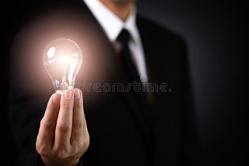 Conceito do neg?cio Ampola da lâmpada da terra arrendada do homem de negócios contra o backgroun escuro imagem de stock royalty free