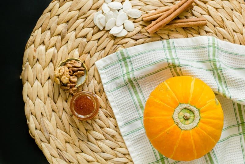 Conceito do outono Abóbora, sementes, mel, nozes e varas de canela pequenos em um guardanapo do círculo do jacinto de água sobre foto de stock royalty free