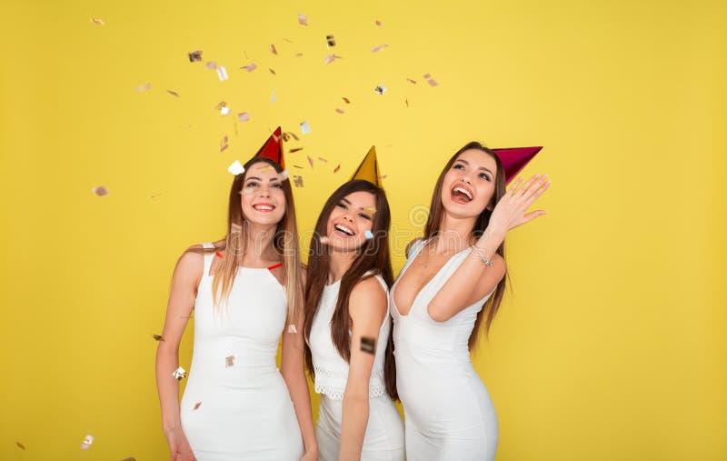 Conceito do partido e dos feriados Três mulheres do encanto em lantejoulas luxuosas do brilho vestem a dança e ter do divertiment imagens de stock royalty free