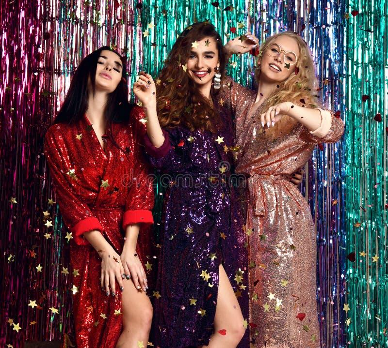 Conceito do partido e dos feriados Tr?s mulheres do encanto em lantejoulas luxuosas do brilho vestem ter o divertimento fotografia de stock royalty free