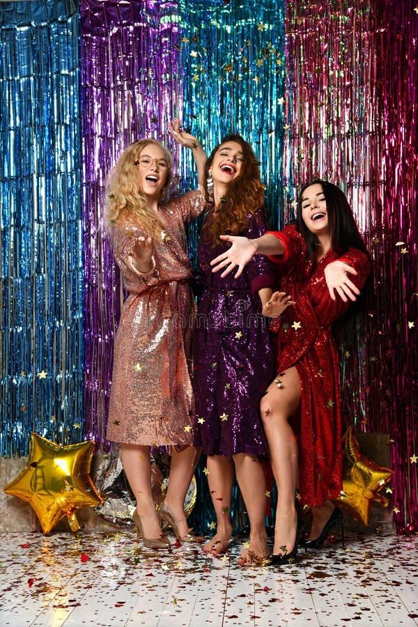 Conceito do partido e dos feriados Tr?s mulheres do encanto em lantejoulas luxuosas do brilho vestem ter o divertimento fotos de stock royalty free
