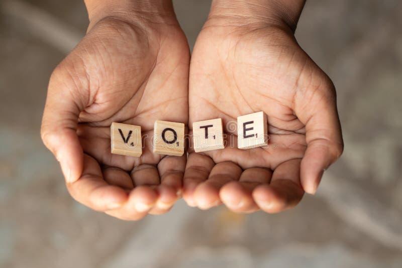 Conceito do pedido pelos votos, letras de madeira no gesto colocado da exibição da mão do pedido, recebendo fotos de stock royalty free