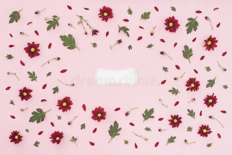 Conceito do per?odo menstrual Prote??o da higiene da mulher Almofada feminino da higiene do algod?o no fundo cor-de-rosa com flor fotografia de stock