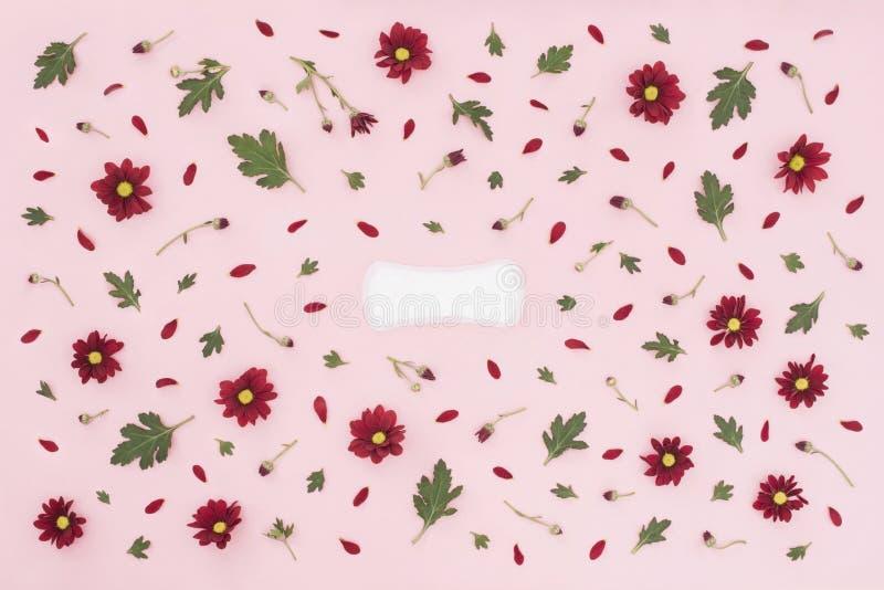 Conceito do per?odo menstrual Prote??o da higiene da mulher Almofada feminino da higiene do algod?o no fundo cor-de-rosa com flor fotos de stock
