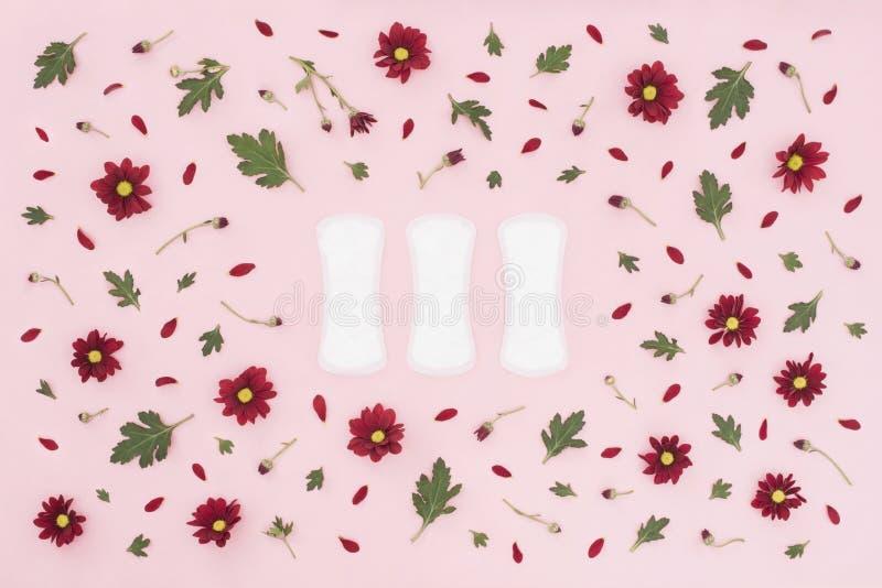 Conceito do per?odo menstrual Prote??o da higiene da mulher Almofadas femininos da higiene do algod?o no fundo cor-de-rosa com fl imagens de stock