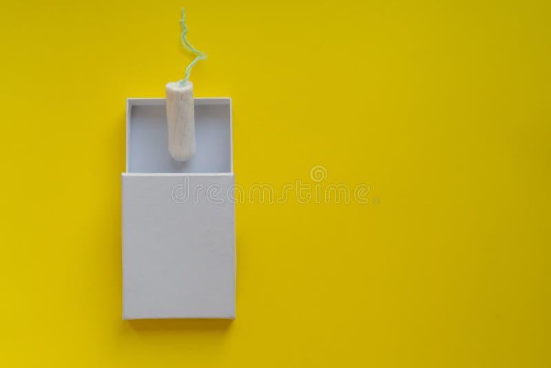 Conceito do per?odo menstrual Prote??o da higiene da mulher Tampão do algodão em um boxon branco no fundo amarelo Espa?o e modelo foto de stock royalty free