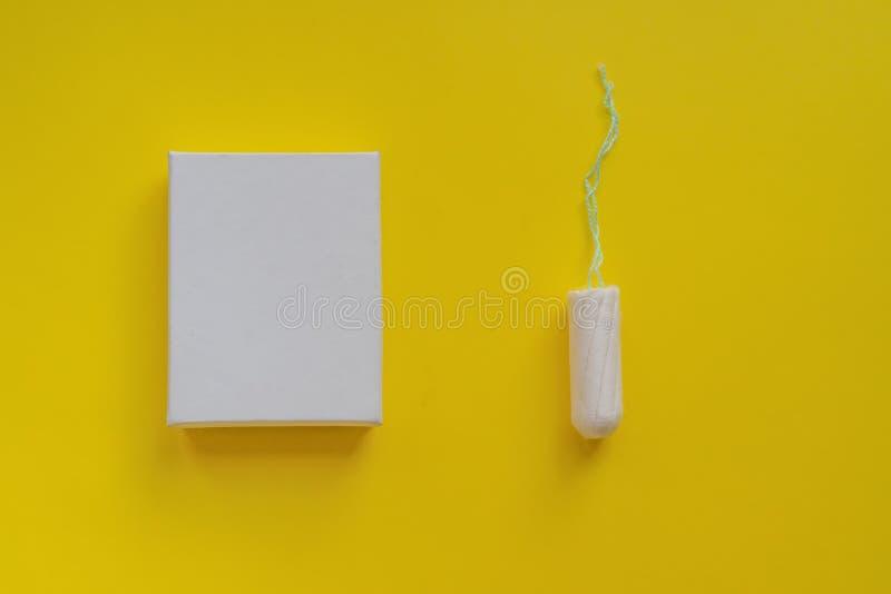Conceito do per?odo menstrual Prote??o da higiene da mulher Tampão do algodão em um boxon branco no fundo amarelo Espa?o e modelo imagem de stock