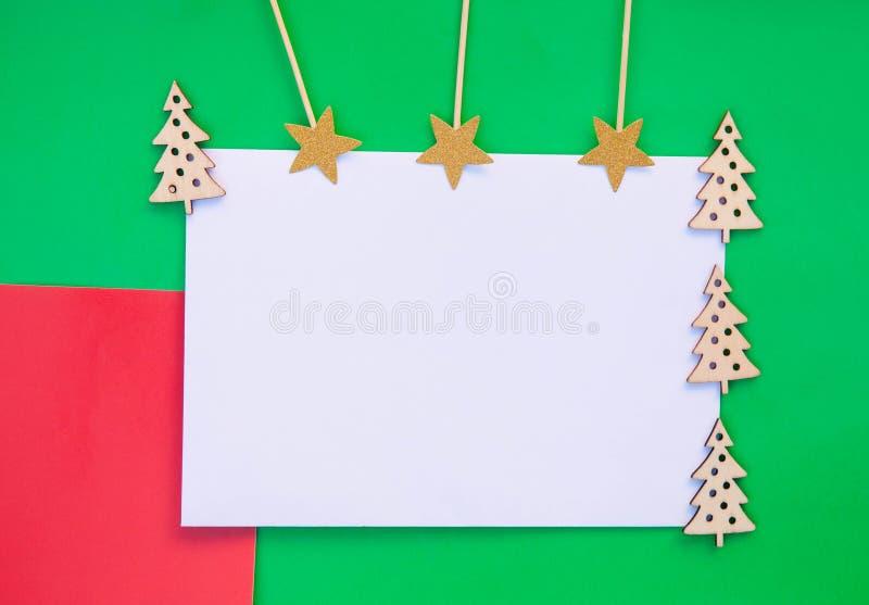 conceito do planeamento do Natal Árvores de Natal e estrelas de madeira do ouro no fundo verde e vermelho com placa limpa branca  foto de stock