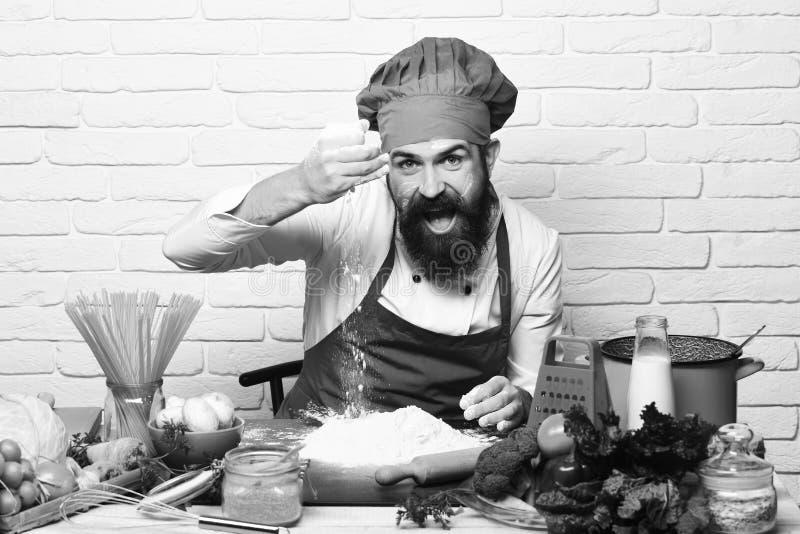Conceito do processo de cozimento O cozinheiro chefe faz a massa Homem com jogos da barba com farinha foto de stock