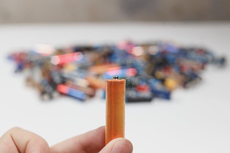 Conceito do recicl Pilha alcalina usada à disposição e muitas pilhas alcalinas borradas no fundo foto de stock