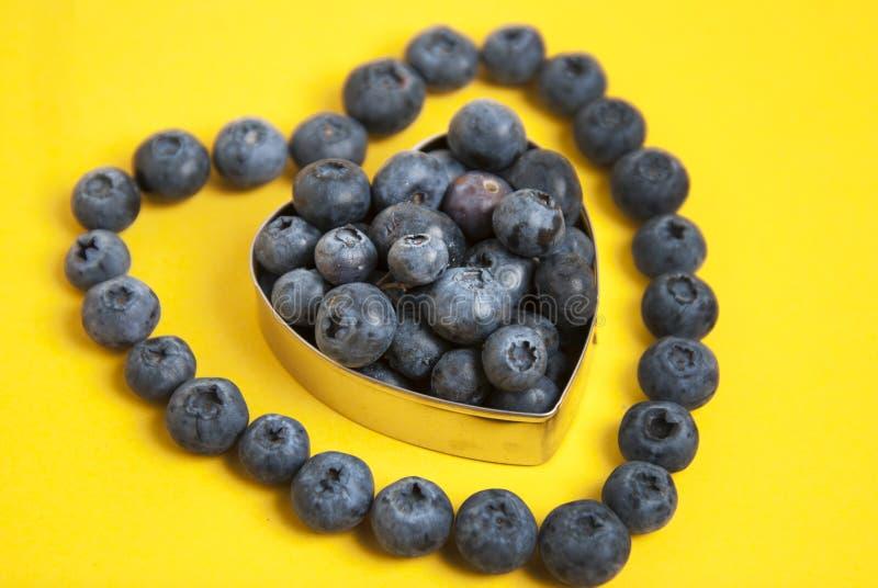 Conceito do símbolo da forma do coração do mirtilo para comer e estilo de vida saudáveis Isolado no fundo amarelo fotos de stock