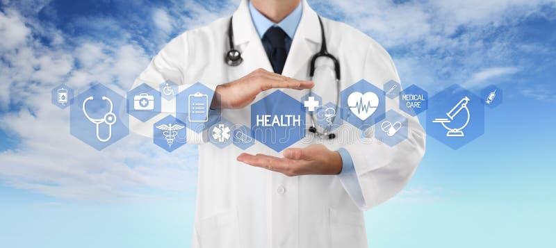 Conceito do seguro da cobertura médica, doutor das mãos cobrindo símbolos e ícones no fundo do céu, no espaço da cópia e no molde imagem de stock