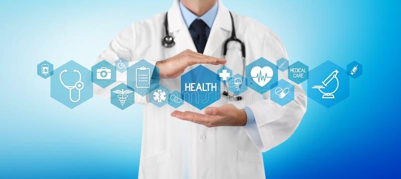Conceito do seguro da cobertura médica, doutor das mãos cobrindo símbolos e ícones no fundo, no espaço da cópia e no molde azuis  fotografia de stock
