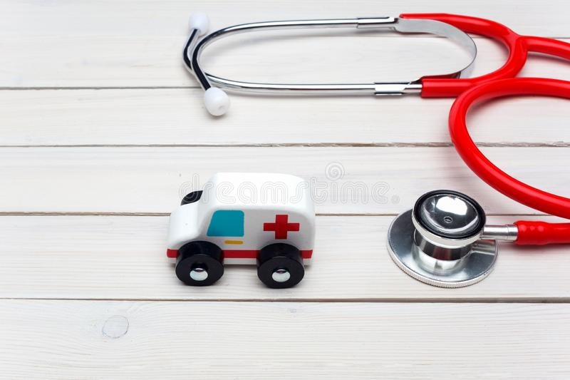 Conceito do serviço de ambulância Brinquedo do veículo da ambulância perto do estetoscópio no fundo de madeira branco imagens de stock royalty free