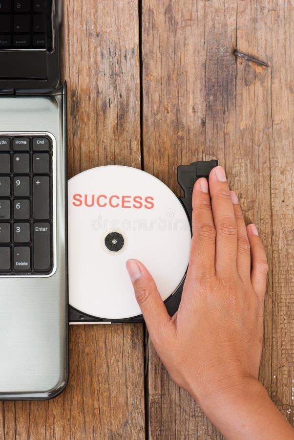 Conceito do sucesso com o portátil do disco compacto na madeira b imagens de stock