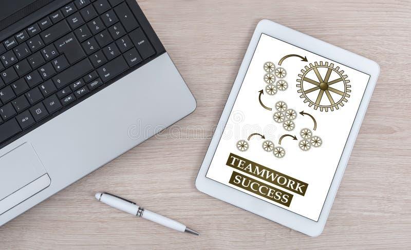 Conceito do sucesso dos trabalhos de equipa em uma tabuleta digital imagem de stock royalty free