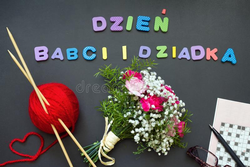 Conceito do sumário do dia das avós com palavras cruzadas e o ramalhete de confecção de malhas das flores foto de stock