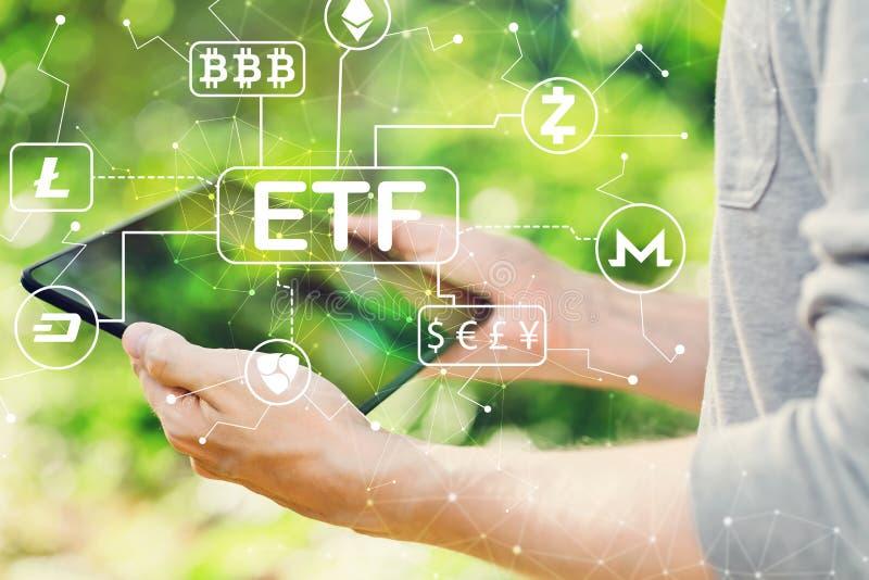 Conceito do tema de Cryptocurrency ETF com o homem que guarda sua tabuleta fotos de stock royalty free