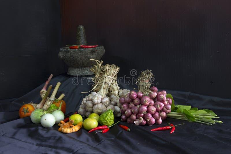 Conceito do tempero Ingrediente tailandês da erva, ervas culinárias frescas e especiarias no fundo preto da tela com um pilão e u fotografia de stock