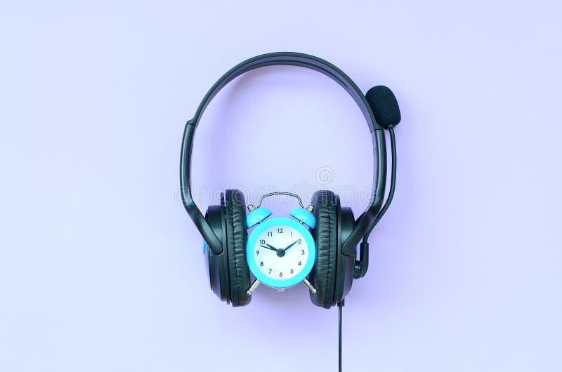 Conceito do tempo à música de escuta Despertador e fones de ouvido fotografia de stock