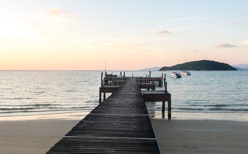 Conceito do tempo de férias, trajeto de madeira macio do filtro de cor do foco entre Crystal Clear Blue Sea e céu foto de stock royalty free