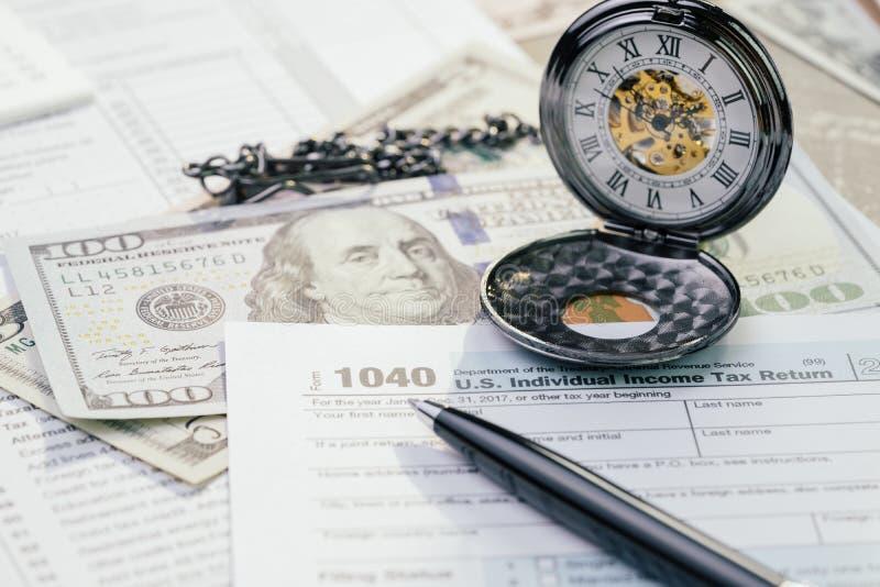 Conceito do tempo do imposto em abril, formulário de enchimento individual do imposto de renda dos E.U. da pena 1040 com as cédul imagens de stock