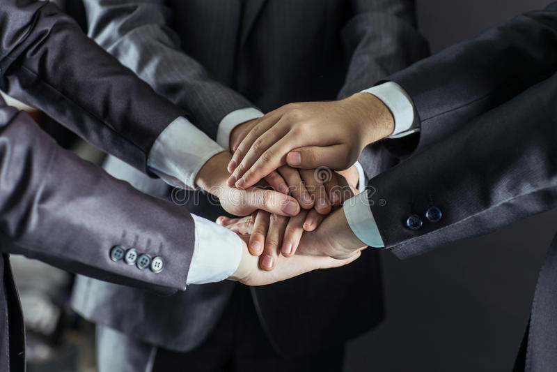 Conceito do trabalho da equipe: um close-up das mãos de equipes do negócio, empilhadas uma em outra imagem de stock